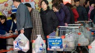 Los clientes de un supermercado con bolsas de plástico.