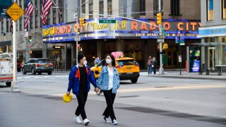 In this May 13, 2020, file photo, people wear protective face masks outside Radio City Music Hall during the coronavirus pandemic in New York City.