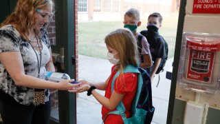 In this Aug. 5, 2020, file photo, wearing masks to prevent the spread of COVID19, elementary school students use hand sanitizer before entering school for classes in Godley, Texas.