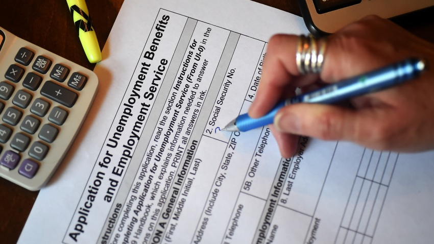 In this April 16, 2020, photo illustration, a person files an application for unemployment benefits in Arlington, Virginia.