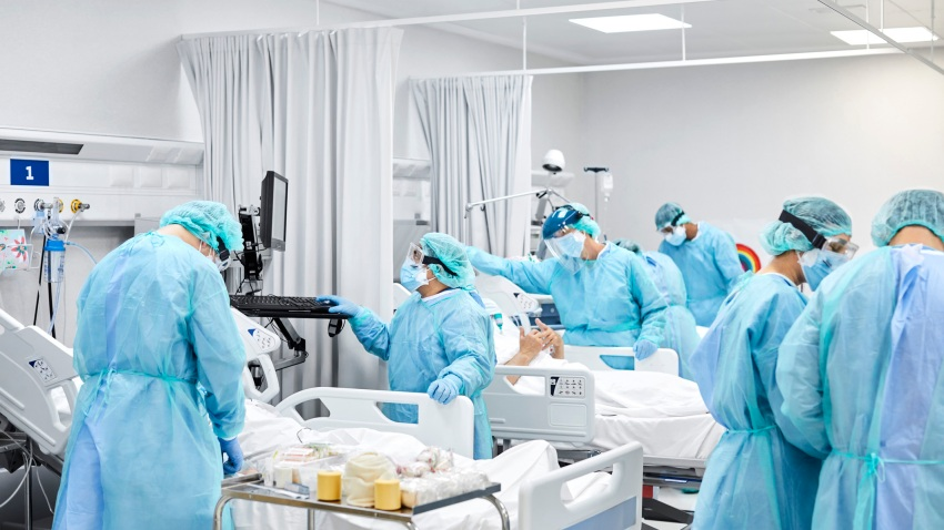 Healthcare coworkers working in ICU. Doctors and nurses wearing protective coveralls. They are at hospital during COVID-19.
