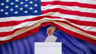 Una mano sale de una bandera de Estados Unidos y deposita un sobre lo deposita un papel en una urna de votación