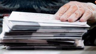 Una mano con guante se posa encima de sobres que contienen votos