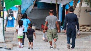 Migrantes caminan entre casas de campaña