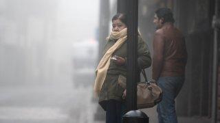 Dos personas en la calle envuelta en bruma por frío