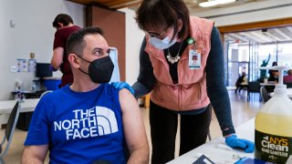 Marx Johny Gerez, of Binghamton, N.Y., who was living in Venezuela until just over a year ago, speaks with Physician Assistant Judy Andrews before receiving a COVID-19 vaccine at a pop-up clinic at the American Civic Association (ACA) in Binghamton