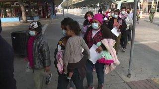 Foto de migrantes haciendo fila en la central de autobuses de McAllen.