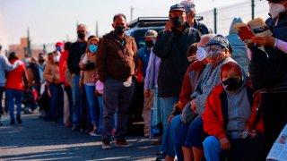 Personas mayores de 60 años hacen fila para ser vacunados