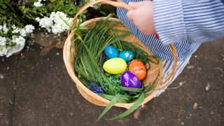 A child's hand holds a wicker basket containing plastic eggs.