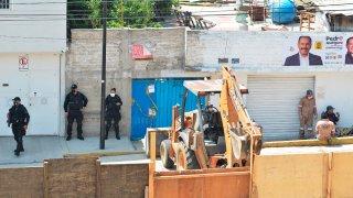 Equipo de remoción en la calle donde está la vivienda de un presunto feminicida serial en México